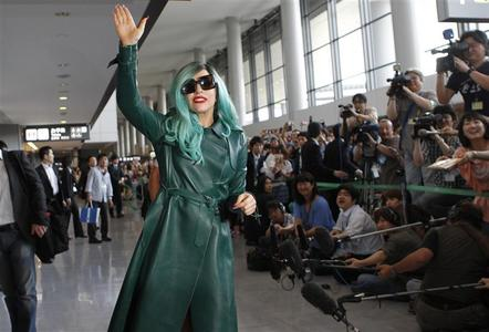 Singer Lady Gaga waves at the media upon her arrival at Narita International Airport near Tokyo, June 21, 2011. REUTERS/Toru Hanai