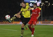 <p>Juanan pour Düsseldorf à la lutte avec Kevin Groisskreutz (en jaune) du Borussia. Le Borussia Dortmund s'est contenté d'un match nul contre le Fortuna Düsseldorf (1-1), mardi, un résultat qui permet aux champions d'Allemagne de consolider leur deuxième place en Bundesliga mais qui les laisse encore loin du Bayern Munich. /Photo prise le 27 novembre 2012/REUTERS/Ina Fassbender</p>