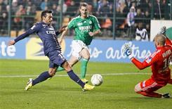 <p>Le Parisien Ezequiel Lavezzi (à gauche) face au gardien stéphanois Stéphane Ruffier. L'AS Saint-Etienne s'est qualifiée mardi soir pour les demi-finales de la Coupe de la Ligue en battant le Paris Saint-Germain au bout de la prolongation (0-0) puis de la séance de tirs au but (5-3). /Photo prise le 27 novembre 2012/REUTERS/Robert Pratta</p>