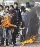 <p>Manifestantes opositores al presidente egipcio Mohamed Mursi encienden bombas de gasolina para provocar disturbios con la policiía cerca a la plaza Tahrir en El Cairo. 29 de noviembre, 2012. REUTERS/Amr Abdallah Dalsh. La Asamblea que está redactando la nueva Constitución de Egipto comenzará a votar un borrador final el jueves, una medida que los aliados del presidente Mohamed Mursi esperan que ayude a poner fin a una crisis generada por la firma de un decreto que expandía los poderes del mandatario.</p>