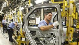 <p>Foto de archivo de unos trabajadores en la línea de ensamblaje de una planta de Renault en Sao Jose dos Pinhais, Brasil, ago 2 2012. La producción industrial brasileña registró en octubre su primer repunte anual en más de un año, debido a que una rebaja de impuestos a los autos ayudó a sustentar una incipiente recuperación en el asediado sector manufacturero local. REUTERS/Rodolfo Buhrer</p>