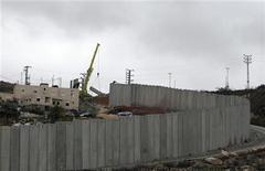 <p>Una grúa levanta un bloque de concreto en la barrera Shuafat en Cisjordania, dic 5 2012. Israel avanzó el miércoles con sus planes para construir unos 3.000 hogares para colonos en una de las zonas más sensibles de la ocupada Cisjordania, mientras que la Unión Europea convocó al enviado israelí para sumar su voz a una ola de reclamos internacionales contra el proyecto expansionista. REUTERS/Ammar Awad</p>