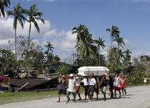 <p>Transport d'un cercueil à New Bataan, dans la Vallée de Compostela. Les populations du sud des Philippines, balayé par le passage du typhon Bopha, ont commencé vendredi à enterrer leurs morts tandis que les secours poursuivaient les recherches. /Photo prise le 6 décembre 2012/REUTERS/Erik De Castro</p>