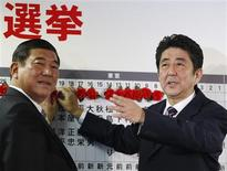 <p>Shinzo Abe (à droite), leader du PLD et ancien Premier ministre japonais, avec le secrétaire général du parti Shigeru Ishiba. Le Parti libéral démocrate (PLD), qui prône plus de fermeté à l'égard de la Chine, a largement remporté dimanche les élections législatives anticipées au Japon, renvoyant dans l'opposition le Parti démocrate (PDJ) après une parenthèse de trois ans. /Photo prise le 16 décembre 2012/REUTERS/Yuriko Nakao</p>