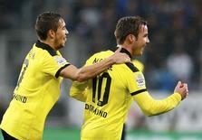 <p>Mario Götze (à droite), du Borussia Dortmund, félicité par son coéquipuer Moritz Leitner après son but contre Hoffenheim dimanche. Le champion en titre a surclassé son adversaire du jour 3-1, s'assurant ainsi de passer la trêve à la troisième place de la Bundesliga à 12 points du premier, le Bayern Munich, et à trois du deuxième, Leverkusen. /Photo prise le 16 décembre 2012/REUTERS/Ralph Orlowski</p>