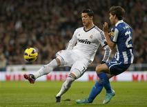 <p>L'attaquant portugais du Real Madrid Cristiano Ronaldo (à gauche), à la lutte avec le défenseur de l'Espanyol Barcelone Victor Alvarez, dimanche sur la pelouse du stade Santiago Bernabeu. Battu il y a quatre jours par le Celta Vigo en Coupe du Roi (2-1), le Real Madrid a de nouveau flanché dimanche en concédant en fin de match un match nul 2-2 face au club catalan. /Photo prise le 16 décembre 2012/REUTERS/Juan Medina</p>