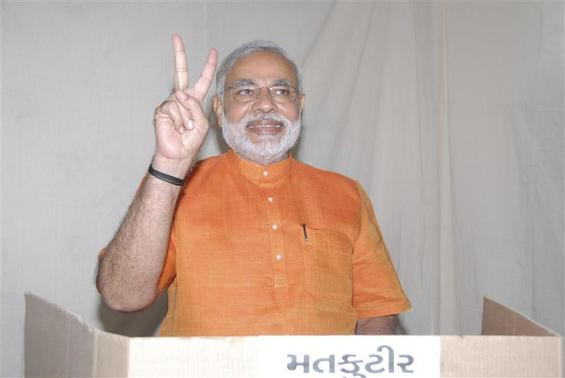 Gujarat Chief Minister Narendra Modi gestures as he casts his vote during the second phase of state elections in Ahmedabad December 17, 2012. REUTERS/Gujarat Information Department/Handout