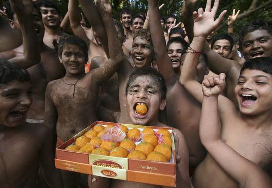 Boys who practice wrestling hold up a box of sweets in Chandigarh August 12, 2012. REUTERS/Ajay Verma/Files