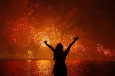 A woman celebrates the New Year as she watches fireworks exploding above Copacabana beach in Rio de Janeiro January 1, 2013. More than two million people gathered along Rio's most famous beach to witness the 20-minute display and celebrate the beginning of a new year. REUTERS/Pilar Olivares