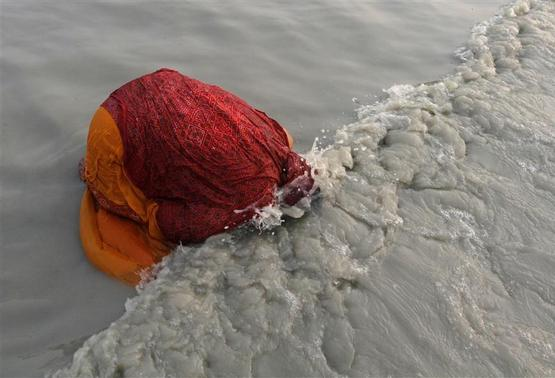 A female Hindu pilgrim takes a dip at the confluence of the Ganges river and the Bay of Bengal at Sagar Island, south of Kolkata, January 14, 2013. REUTERS/Rupak De Chowdhuri