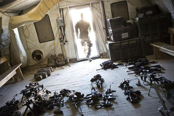 A soldier from 1st Platoon, Alpha Company, 1st Battalion, 36th Infantry leaves a room while checking the inventory of weapons at Strong Point DeMaiwand, Maywand District, Kandahar Province, Afghanistan, January 20, 2013. REUTERS/Andrew Burton