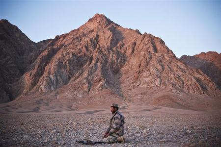 A member of the Afghan National Police prays at sunset before the detonation of confiscated improvised explosive devices (IEDs) near Combat Outpost Hutal in Maiwand District, Kandahar Province, Afghanistan, January 21, 2013. REUTERS/Andrew Burton