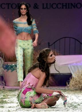 Spanish model Laura Sanchez kneels on the floor after stumbling during a Vitorio & Luccino fashion show in Madrid, September 6, 2000. REUTERS-Andrea Comas