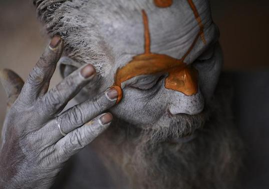 A Hindu sadhu (holy man) applies paint to his forehead at his ashram on the premises of Pashupatinath Temple in Kathmandu March 4, 2013. Hindu holy men from Nepal and India come to this temple to take part in the Shivaratri festival, which this year falls on March 10. Celebrated by Hindu devotees all over the world, Shivaratri is dedicated to Lord Shiva, and holy men mark the occasion by praying, smoking marijuana or smearing their bodies with ashes. REUTERS/Navesh Chitrakar