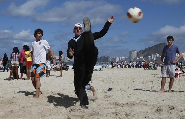 A priest from Argentina plays soccer on Copacabana beach where Pope Francis will return for a Via Crucis at night in Rio de Janeiro, July 26, 2013.  REUTERS-Sergio Moraes