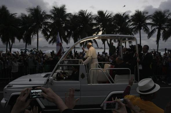 Pope Francis greets the crowd as he rides in the popemobile along Copacabana Beach in Rio de Janeiro, July 26, 2013.   REUTERS-Pilar Olivares