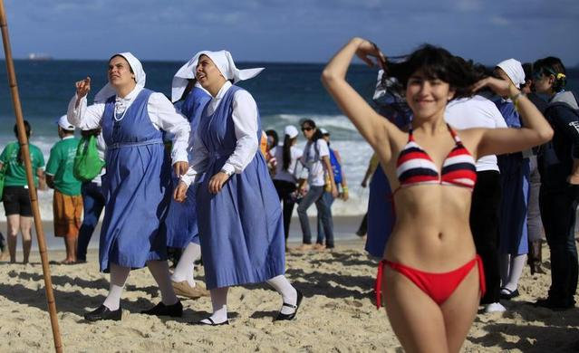 Nuns and sunbathers wait for the arrival of Pope Francis on Copacabana beach in Rio de Janeiro, July 26, 2013. REUTERS-Ricardo Moraes