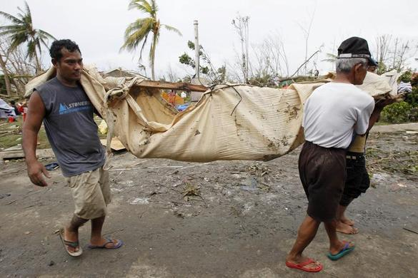 Residents carry the body of a loved one after super Typhoon Haiyan battered Tacloban city, central Philippines, November 9, 2013. REUTERS-Romeo Ranoco