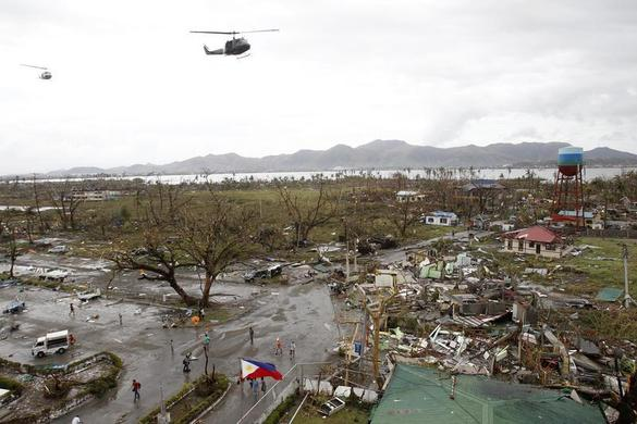 Helicopters hover over the damaged area after super Typhoon Haiyan battered Tacloban city, central Philippines, November 9, 2013. REUTERS-Romeo Ranoco