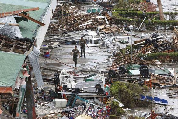 Soldiers walks past the damaged area of an airport after super Typhoon Haiyan battered Tacloban city, central Philippines, November 9, 2013. REUTERS-Romeo Ranoco