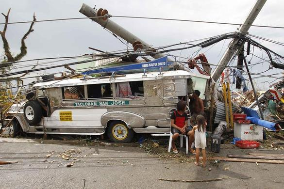 Survivors who lost their homes use a Jeepney public bus as shelter after a super Typhoon Haiyan battered Tacloban city, central Philippines November 9, 2013. REUTERS-Romeo Ranoco