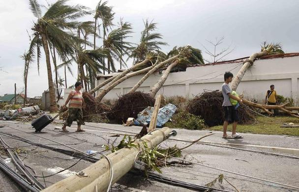 Survivors walks past uprooted palm trees after super Typhoon Haiyan battered Tacloban city, central Philippines November 9, 2013. REUTERS-Romeo Ranoco