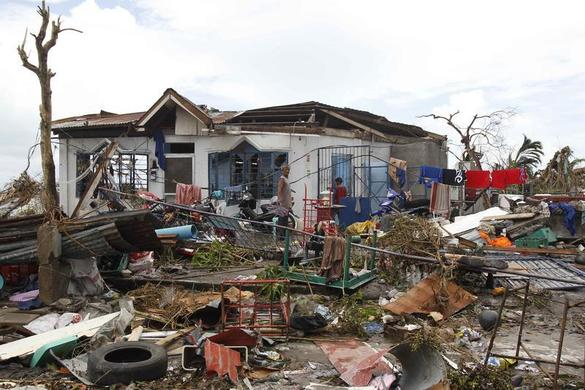 Survivors walk near their damaged house after super Typhoon Haiyan battered Tacloban city, central Philippines November 9, 2013. REUTERS-Romeo Ranoco