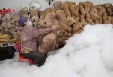 Un ouvrier d'une usine de jouets en Chine termine la fabrication d'un ours en peluche, à Wuhan, dans la province de Hubei. L'économie chinoise a fortement ralenti au cours des deux premiers mois de l'année.La croissance de l'investissement, des ventes de détail et de la production industrielle est tombée à son plus bas niveau depuis plusieurs années. /Photo prise le 15 janvier 2014/REUTERS