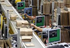Workers pack boxes at Amazon's logistics centre in Graben near Augsburg December 16, 2013. Workers at Amazon.com's German operations were set to go on strike on Monday, in the middle of the crucial Christmas holiday season, in a dispute over pay that has been raging for months. The Verdi union said workers would strike in Amazon's logistic centres in Bad Hersfeld and Leipzig and, for the first time, in Graben. REUTERS/Michaela Rehle (GERMANY - Tags: BUSINESS EMPLOYMENT) - RTX16KXG