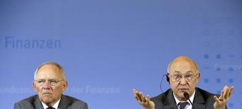 """Conférence de presse à Berlin du ministre des Finances Michel Sapin (à droite) et de son homologue allemand Wolfgang Schäuble. Les ministres français des Finances et celui de l'Economie Arnaud Montebourg, deux hommes si différents que leur cohabitation à Bercy a fait naître des craintes de cacophonie au gouvernement, ont défendu chacun leur priorité lundi. Le premier a promis le sérieux budgétaire tandis que le second a insisté sur le besoin de croissance, jugeant les comptes publics """"accessoires"""". /Photo prise le 7 avril 2014/REUTERS/Fabrizio Bensch"""