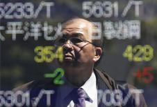 Мужчина отражается в экране с котировками у брокерской конторы в Токио 14 апреля 2014 года. Азиатские фондовые рынки, кроме Японии, снизились во вторник под влиянием геополитических рисков и местных новостей. REUTERS/Issei Kato