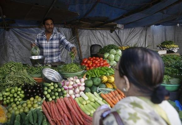 A customer speaks to a vendor while buying vegetables from a street side shop in Mumbai January 13, 2014. REUTERS/Danish Siddiqui/Files