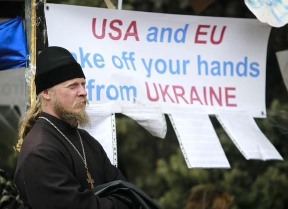 An Orthodox priest stands in a camp of pro-Russian protesters in front of the seized office of the SBU state security service in Luhansk, eastern Ukraine April 15, 2014. REUTERS/Shamil Zhumatov