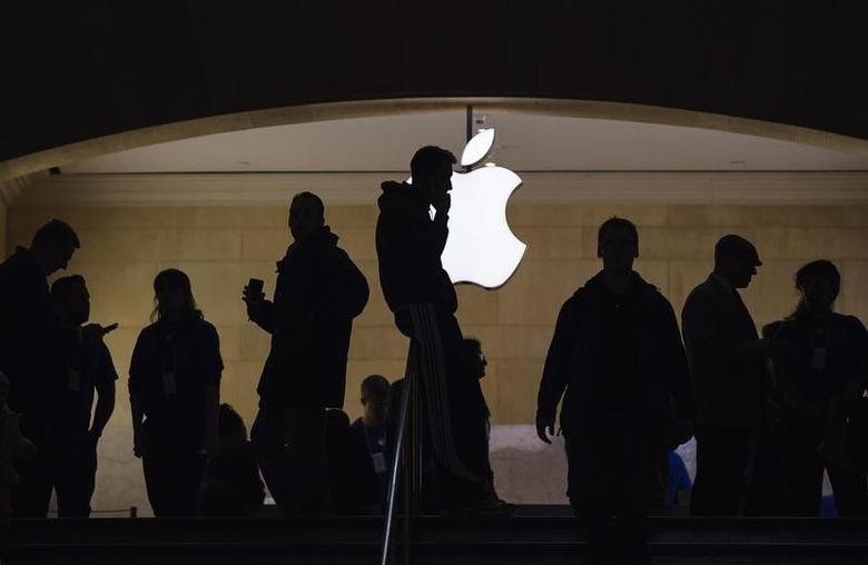 A man talks on his telephone as customers walk through an Apple store in Grand Central Terminal in New York, March 15, 2013.  REUTERS/Lucas Jackson/Files