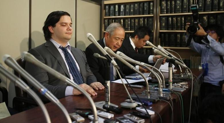 Mark Karpeles (L), chief executive of Mt. Gox, attends a news conference at the Tokyo District Court in Tokyo February 28, 2014. Mt. Gox, once the world's biggest bitcoin exchange, filed for bankruptcy protection on Friday, saying it may have lost all of its investors' virtual coins due to hacking into its faulty computer system. Karpeles, bowing in contrition and wearing a suit instead of his customary T-shirt, apologised in Japanese at a news conference for the company's collapse, blaming ''a weakness in our system.''    REUTERS/Yuya Shino (JAPAN - Tags: CRIME LAW BUSINESS) - RTR3FTG4