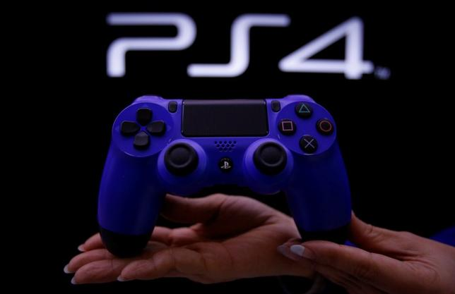 A staff at the PlayStation 4 launch event poses with the PlayStation 4's game controller before its domestic launch event at the Sony Showroom in Tokyo February 21, 2014. REUTERS/Yuya Shino/Files