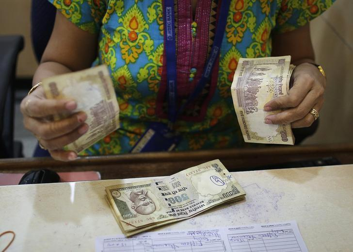 A cashier counts Indian rupee currency notes inside a bank in Mumbai December 6, 2013. REUTERS/Danish Siddiqui