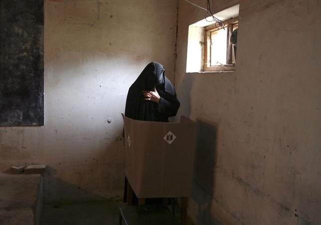 A veiled Muslim woman casts her vote inside a polling station in Doda district, north of Jammu April 17, 2014. REUTERS/Mukesh Gupta