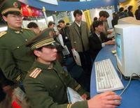 """Офицер вооруженной милиции Китая сидит в интернете на компьютерной выставке в Пекине 23 марта 1999 года. Китай призвал партнеров по Шанхайской организации сотрудничества - Россию и страны Центральной Азии - усилить контроль над интернетом и предпринять другие шаги, мешая """"внешним силам"""" разжечь революции на постсоветском пространстве. REUTERS/Natalie Behring"""