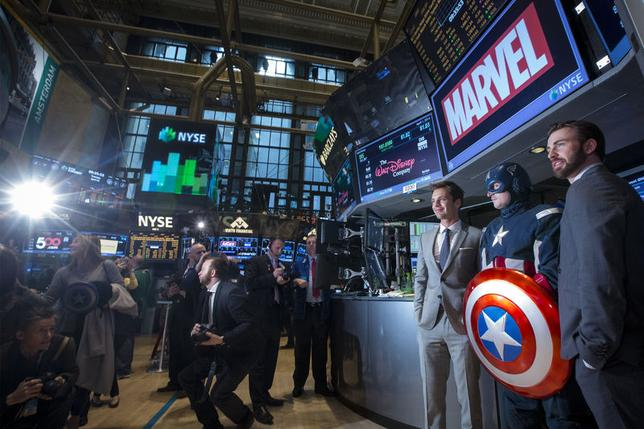 Actors Chris Evans (R) and Sebastian Stan (3rd R) pose for photographs with a man dressed as Captain America on the floor of the New York Stock Exchange April 1, 2014. Evans and Stan rang the opening bell to promote their upcoming movie 'Captain America: The Winter Soldier'. REUTERS/Brendan McDermid (UNITED STATES - Tags: BUSINESS) - RTR3JJ6X
