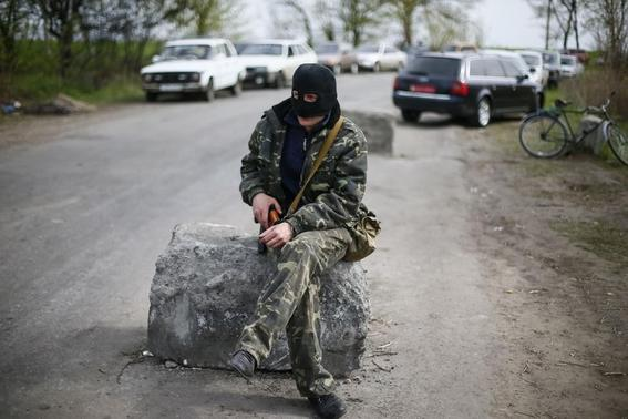 An armed man sits on a rock at a checkpoint that was the scene of an overnight gunfight near the city of Slaviansk April 20, 2014. REUTERS/Gleb Garanich