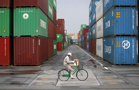 A worker rides a bicycle in a container area at a port in Tokyo April 21, 2014. REUTERS/Toru Hanai