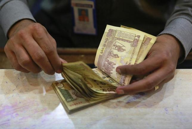 A cashier counts Indian rupee currency notes inside a bank in Mumbai August 5, 2013. REUTERS/Danish Siddiqui/Files