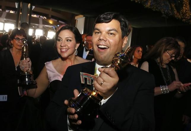 Kristen Anderson-Lopez and Robert Lopez kiss while holding their Oscars for best original song for ''Let it Go'' in the film ''Frozen'' at the Governors Ball at the 86th Academy Awards in Hollywood, California March 2, 2014.  REUTERS/Adrees Latif/Files