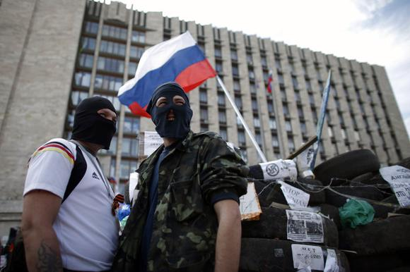 Masked pro-Russia protesters stand guard near a barricade outside a regional government building in Donetsk, in eastern Ukraine April 23, 2014. REUTERS/Marko Djurica
