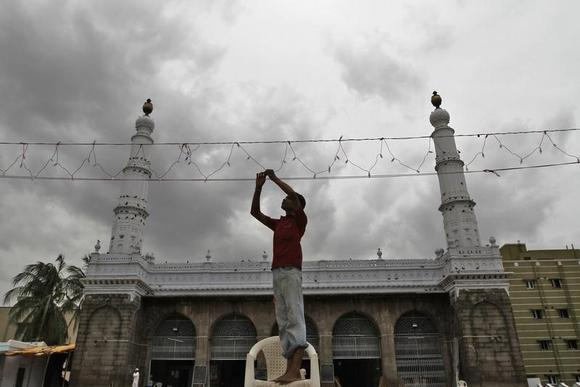 An electrician fixes lights on a mosque against the backdrop of monsoon clouds, during the holy month of Ramadan in the southern Indian city of Chennai August 5, 2013. REUTERS/Babu/Files