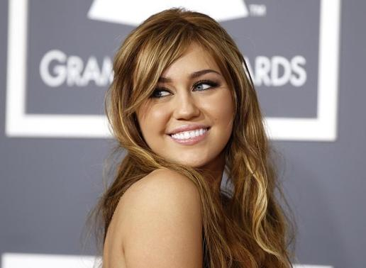 Miley Cyrus poses on arrival at the 53rd annual Grammy Awards in Los Angeles, California February 13, 2011. REUTERS/Danny Moloshok/Files