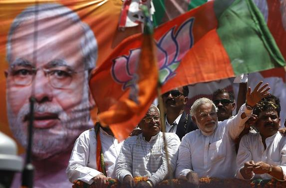 Narendra Modi (2-R) prime ministerial candidate for Bharatiya Janata Party (BJP), waves to his supporters as he arrives to file his nomination papers for the general elections in Varanasi April 24, 2014. REUTERS/Adnan Abidi