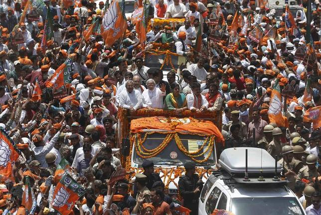 Hindu nationalist Narendra Modi, prime ministerial candidate for India's main opposition Bharatiya Janata Party (BJP), waves to his supporters as he arrives to file his nomination papers for the general elections in Varanasi April 24, 2014. REUTERS/Adnan Abidi