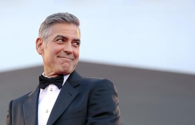 U.S. actor George Clooney smiles as he arrives on the red carpet for the premiere of ''Gravity'' at the 70th Venice Film Festival in Venice August 28, 2013. REUTERS/Alessandro Bianchi/Files